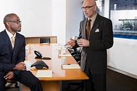 Two businessmen discussing in a board room