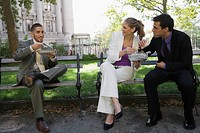 Three business executives eating food on park benches