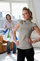 Young woman standing with a young man holding shopping bags in the background