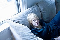 Young blond woman sitting on her living room sofa.