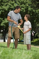 Boy helping father with sprinkler in backyard