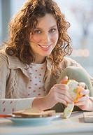 Portrait of woman peeling orange