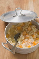 A pan of pumpkin risotto with propped pan lid