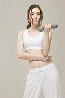 Young woman exercising with dumbbell