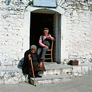 Old man with glasses, sitting on a chair and an old woman with a stick sitting on a step in a village in Greece, Europe