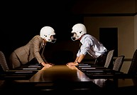 Businessman and businesswoman in face_off wearing football helmets