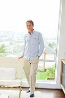 Portrait of man standing in front of living room window