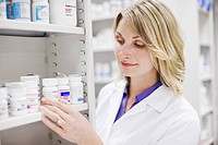 Close up of pharmacist looking at pill bottles on shelf
