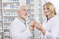 Pharmacists examining label on pill bottle