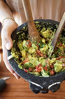 Person Holding a Bowl of Homemade Guacamole
