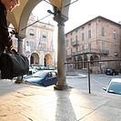 Businessman checks watch heads into historic town center Moncalieri Turin area Italy Piedmont