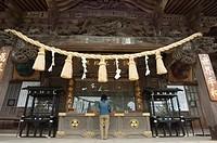 Girl praying at shrine under giant rope, Takao jinja shrine, Takao San mountain, Tokyo, Japan, Asia