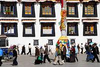 Tibetan people walk by the building of Jokhang Kora Lhasa Tibet China