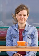 Woman sitting at a cafe drinking coffee
