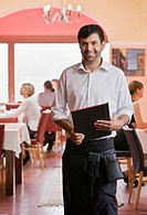 Portrait of waiter with menus in hand