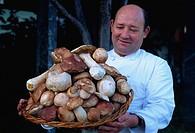 Chef with basket of mushrooms, Lugano, Ticino region, Switzerland, Europe