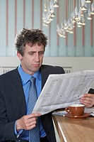 Businessman at bar reading paper, doubt