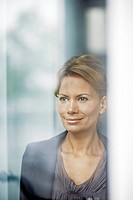 Woman looking through window, smiling