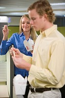 Two young businesspeople eating Chinese food in office, focus on woman in background
