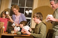 Portrait of family eating Chinese takeout together in dining room