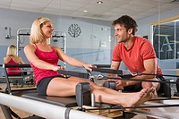 Young woman and young man sitting on Pilates exercise equipment in gym with mirror in background