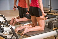 Young woman and young man on Pilates exercise equipment in gym with wall in background