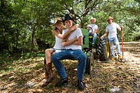 Portrait of young cowboys and cowgirl relaxing near tractor outdoors