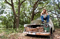 Young blonde cowgirl in cowboy hat sitting on vintage truck outdoors