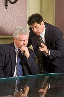 Two multi_ethnic businessmen having discussion in meeting room around glass round table