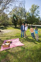 Young happy family playing in park around picnic blanket