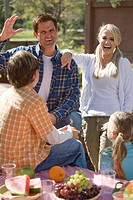 Young happy family at picnic table near campsite