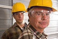 Portrait of mid adult man and senior man wearing goggles and hard hats on construction site