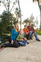 Portrait of young happy family sitting outside looking at camera