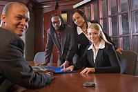 Portrait of four multi_ethnic businesspeople sitting in boardroom around table