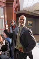 Three multi_ethnic businesspeople in office waiting area, focus on man holding mobile phone