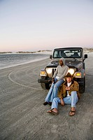 Young interracial couple sitting in front of Jeep at beach, holding beer bottle