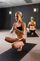 Young woman holding yoga pose in workout studio