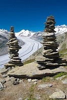 Piled stones to mark the road in the mountains  Valley glacier with its longitudinal moraines of the Glacier Alesht  At the bottom the summits of the ...