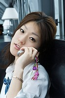 Young female using cell phone, looking at camera