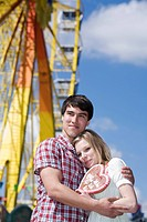 portrait of teenage couple with gingerbread heart at fun fair