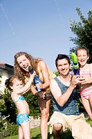 family playing garden with water pistols
