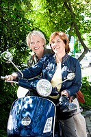portrait of two senior woman sitting on scooter