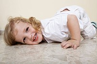 Young child lying on floor laughing
