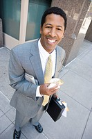 Portrait of businessman with newspaper and sandwich smiling