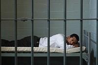 Man lying in prison cell
