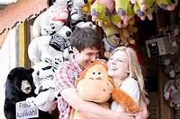 teenage couple at fun fair in close embrace