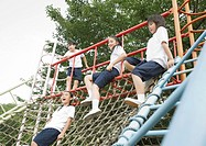 Elementary students sitting on play equipment