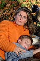 Woman in orange cardigan lies on grass with son