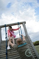 Man and woman climbing up the play equipment