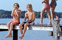 Two Boys with naked Torso eating Bread while two Girls in Bikini walk by _ Snack _ Leisure Time _ Friendship _ Lake